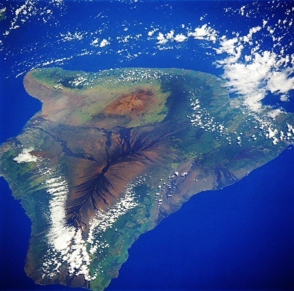 Na zdjęciu satelitarnym wyspa na morzu, wśrodkowej części wzniesienia. Dookoła tereny zielone.