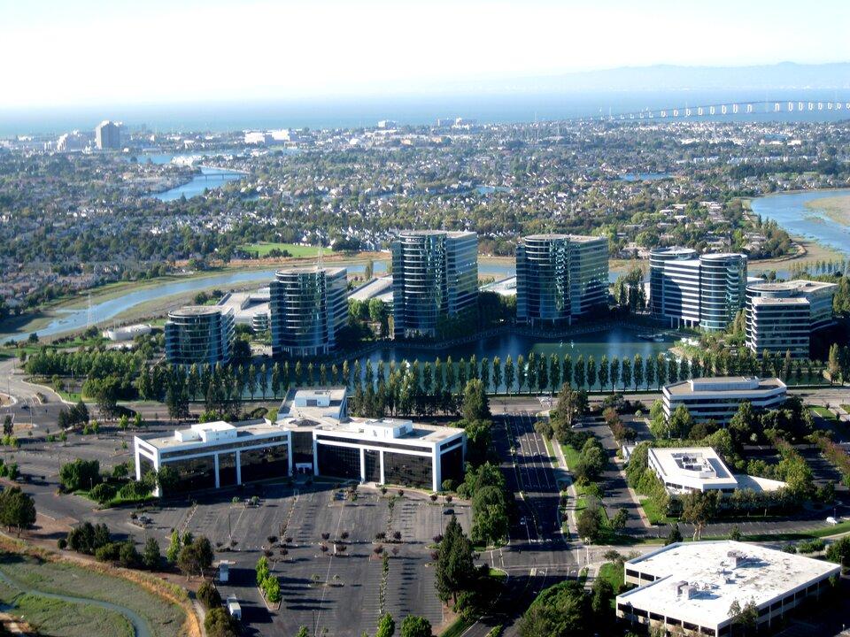 Na zdjęciu nowoczesna zabudowa biurowa. Kilka wieżowców, na pierwszym planie niższe budynki. Całość ładnie zagospodarowana, drzewa rosną wrównych szpalerach, przed biurowcami akwen wodny. Wtle zabudowania izieleń, dalej morze.