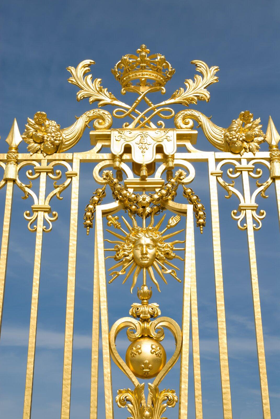 Ilustracja przedstawia bramę Pałacu Królewskiego wWersalu. Jest to złote ibogato zdobione przęsło. Na samym szczycie znajduje się korona.