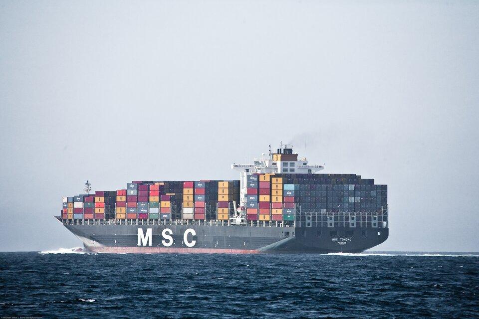 Na zdjęciu statek kontenerowiec zzaładowanymi kontenerami. Stoją na całej powierzchni pokładu, najwyższa warstwa ma siedem kontenerów. Szesnaście kolumn kontenerów na długość statku iszesnaście kolumn kontenerów na szerokość statku.