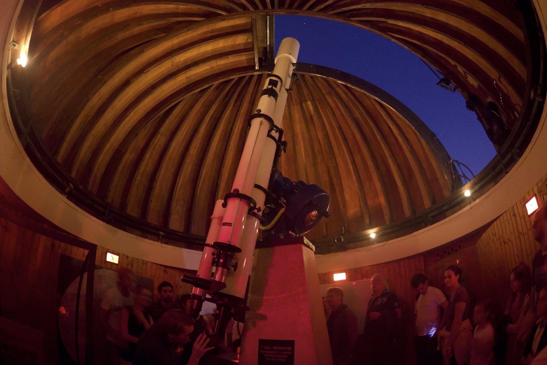 Zdjęcie przedstawia wnętrze obserwatorium wMonachium podczas pokazowej lekcji astronomii. Wkadrze znajduje się długi, ustawiony wpozycji pionowej biały teleskop iotwarta kopuła zwidocznym nocnym niebem. Poniżej wokół teleskopu zebrani ludzie wróżnym wieku. Młody mężczyzna nachylony przed teleskopem spogląda przez okular.