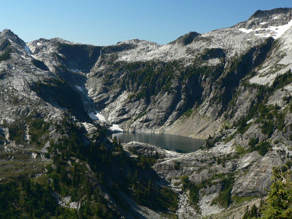 Na zdjęciu strome góry oprawie pionowych stokach. Na płaskim szczycie śnieg. Wcentrum dolina. Wewnątrz doliny okrągły zbiornik wodny.