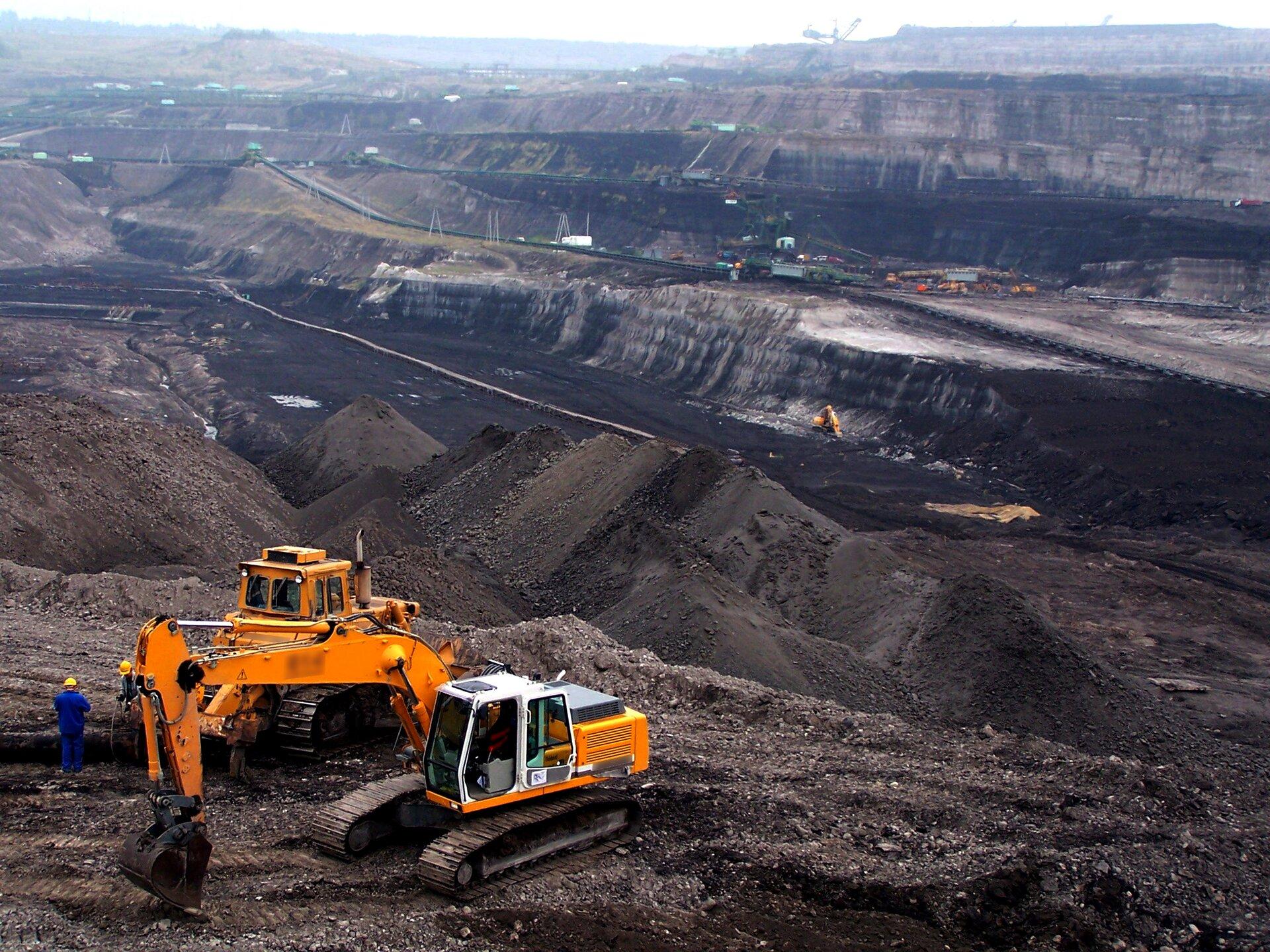 Na zdjęciu kopalnia odkrywkowa. Rozległe wyrobisko. Na pierwszym planie duże hałdy węgla iżółte koparki ipracownicy. Wtle kolejne maszyny.