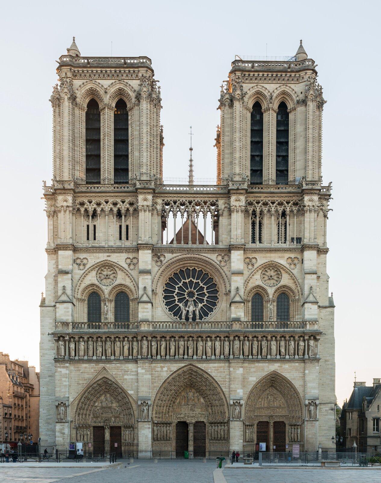 Ilustracja przedstawia Katedrę Notre-Dame wParyżu. Na zdjęciu jest frontowa część katedry ztrzema wejściami, którego obramowania stanowią dekoracyjne portale. Środkowa część to okrągła rozeta na środku idwa dwuczęściowe okna po bokach wformie biforium, również zdobione portalami. Od dolnej części oddzielą ją balustrada. Trzecia cześć katedry zakończona jest dwiema wieżami zdużymi wąskimi otworami okiennymi - biforium. Wieże są kwadratowe, zakończone balustradą. Na ich szczycie widać jeszcze dwie małe okrągłe wieżyczki zakończone daszkiem wkształcie stożka. Wtle między wieżami widać szpiczasty maszt ijasne błękitne niebo.