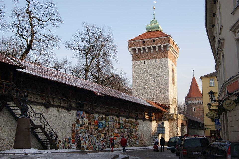 Na zdjęciu fragment murów miejskich, na murze zawieszone obrazy. Wmurach brama wformie wieży.