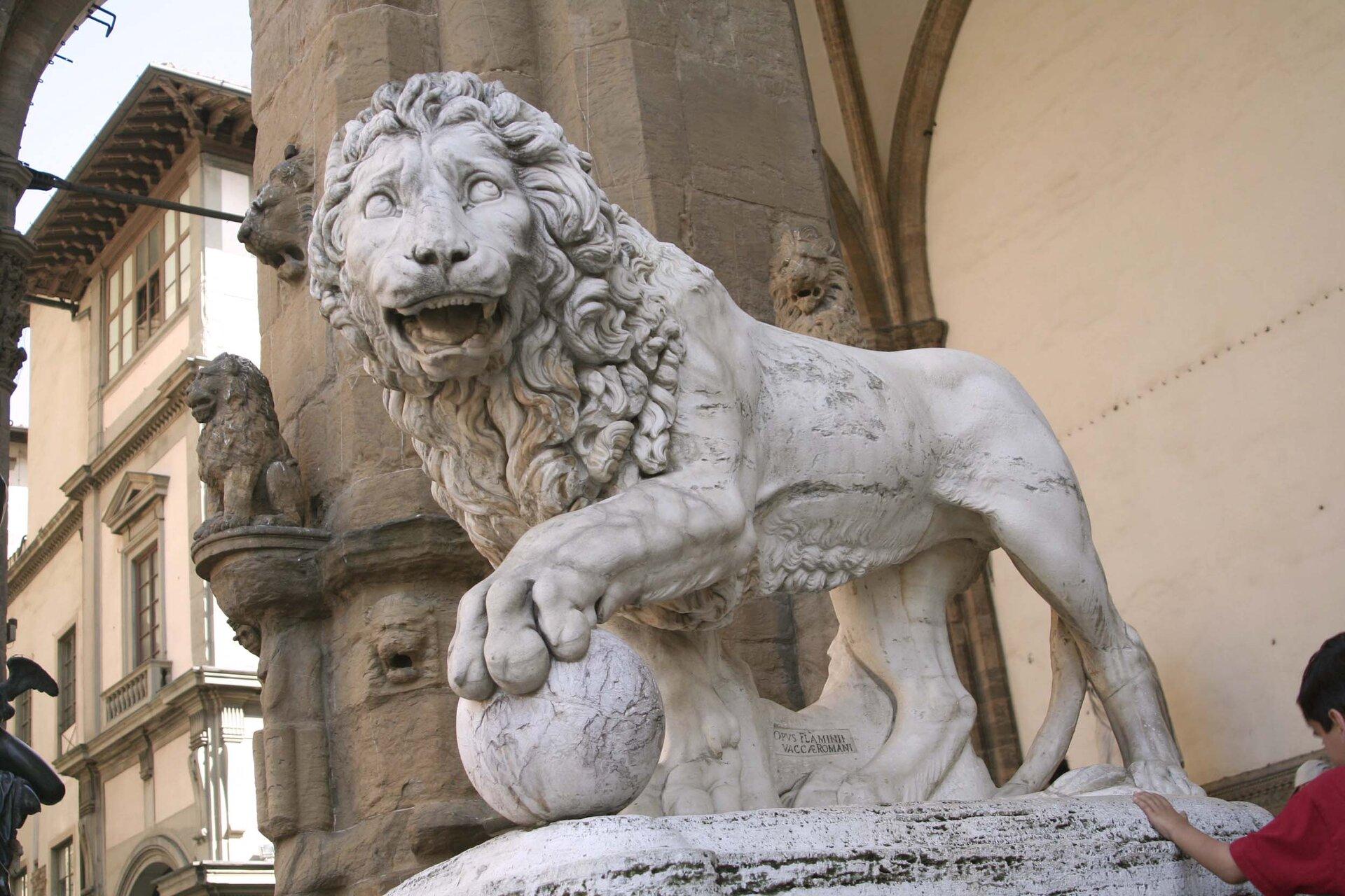 """Ilustracja przedstawia rzeźbę Flaminio Vaccim """"Lew"""". Ukazuje lwa stojącego na cokole obujnej grzywie zgłową odwróconą wlewą stronę, otwartą paszczą. Zwierzę trzyma łapę na kuli. Wtle widoczna jest zabudowa architektoniczna."""