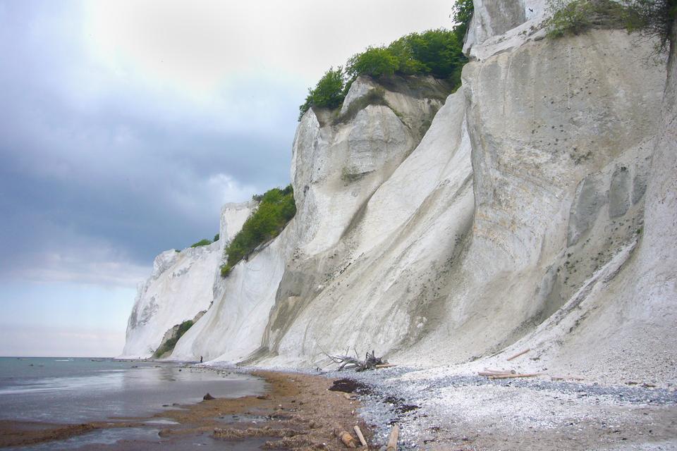 Fotografia przedstawia morskie wybrzeże zdużymi, białymi skałami. Skały te to klify kredowe. Udołu są podmywane przez fale, ana górze rosną na nich zielone krzewy.Fotografia przedstawia na czarnym tle kupkę białego proszku. To tak zwana ziemia okrzemkowa, czyli pancerzyki okrzemek. Ma wiele zastosowań.