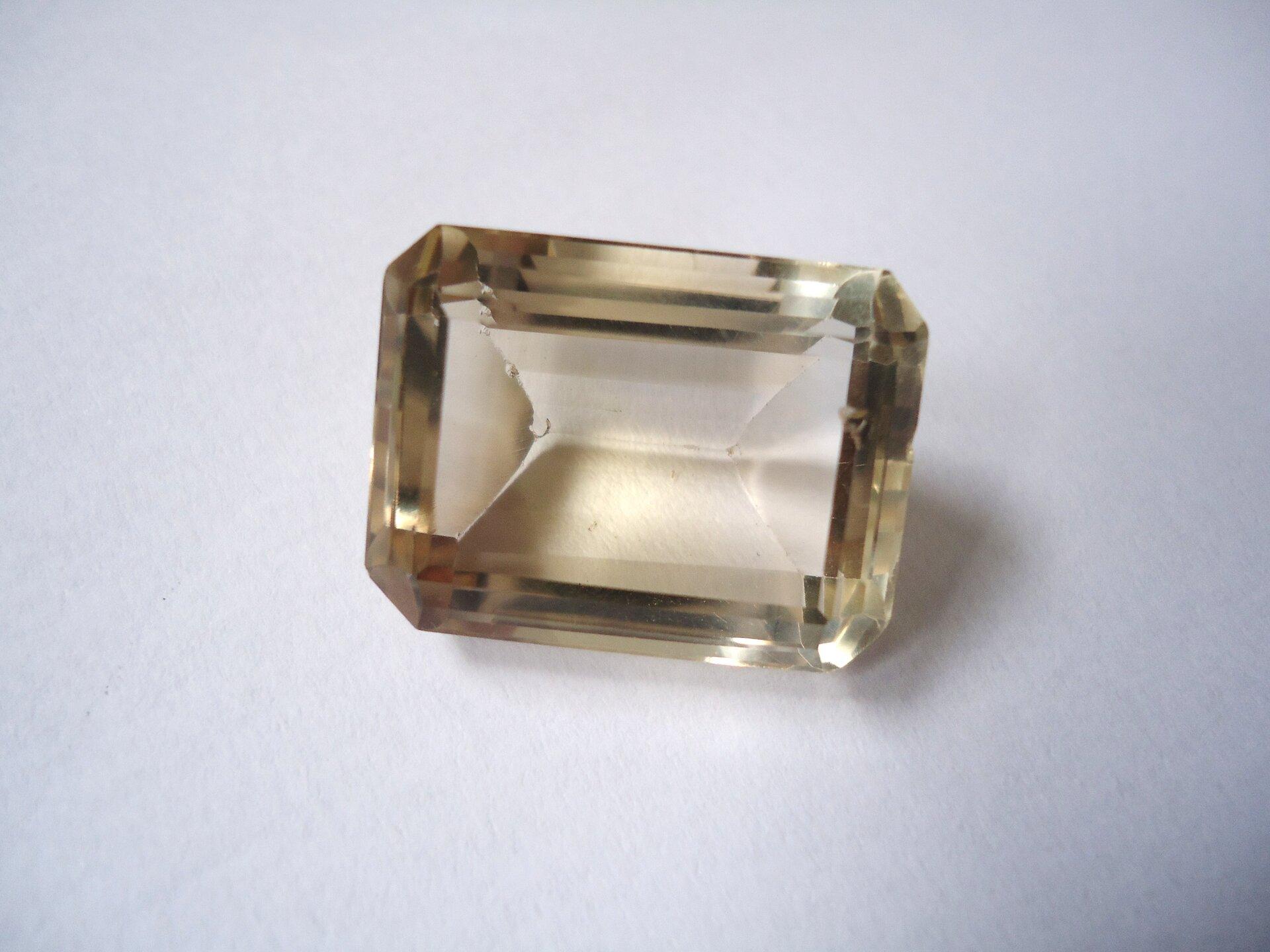 Zdjęcie przedstawia oszlifowany kwarc dymny wformie szlifu szmaragdowego, czyli prostokątnego. Kamień jest bladożółty iprzejrzysty, leży na białym tle.