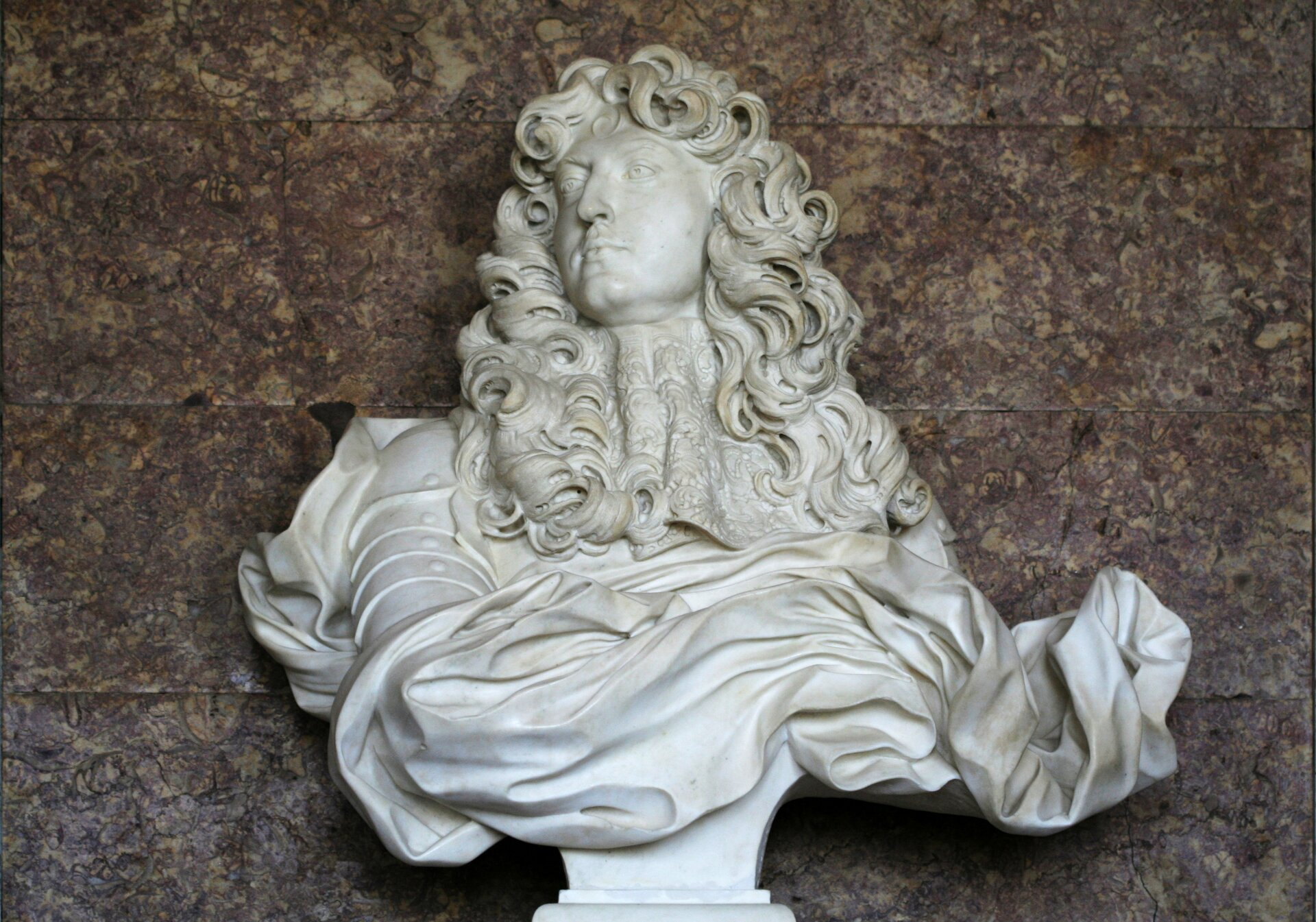 """Ilustracja przedstawia rzeźbę """"Popiersie Ludwika XIV"""" autorstwa Gian Lorenzo Berniniego. Wykonane zbiałego marmuru dzieł ukazuje mężczyznę wśrednim wieku zdługimi, kręconymi włosami spływającymi na ramiona. Postać ubrana jest wzbroję, którą okrywa dynamicznie wyrzeźbiona, pofałdowana draperia. Pod szyją znajduje się misternie wykonany, koronkowy żabot. Głowa mężczyzny zwrócona jest wprawą stronę. Popiersie wyrzeźbione jest na zwężającym się ku dołowi postumencie."""