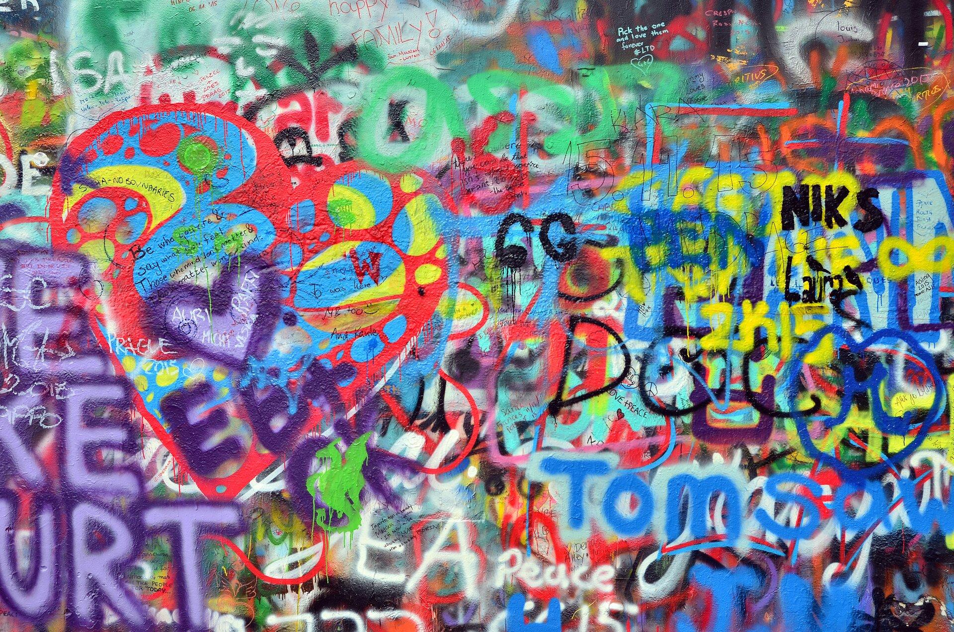 Ilustracja przedstawia fotografię zamalowanej sprayami ściany. Znajdują się na niej różnobarwne napisy oraz motywy graficzne.