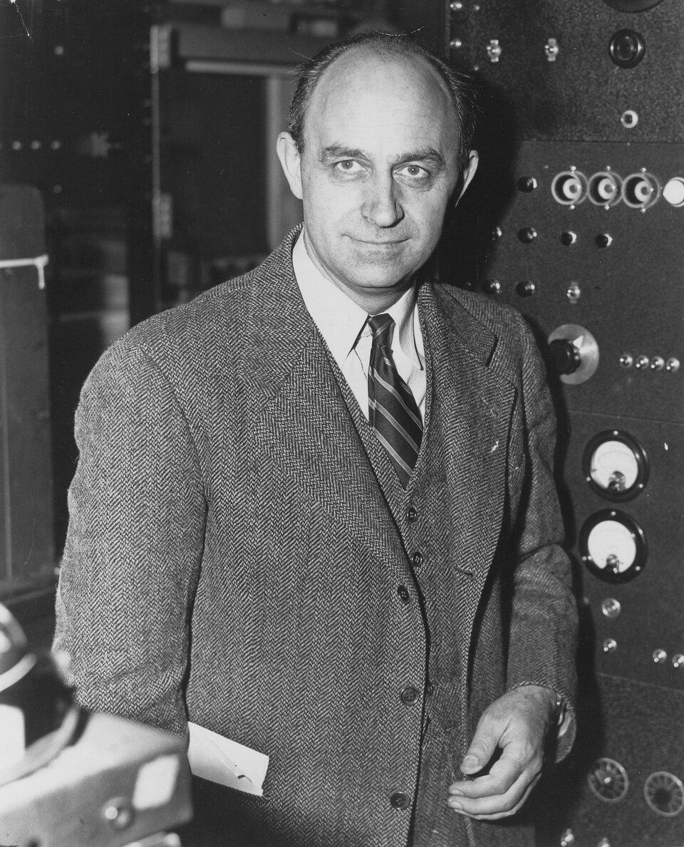 Zdjęcie przedstawia Enrico Fermi. Fotografia czarno-biała. Na zdjęciu mężczyzna wwieku ok. 45 lat, szczupły, łysiejący. Czoło wysokie, linia włosów cofnięta, włosy ciemne. Brwi gęste. Oczy duże. Nos długi. Usta wąskie. Mężczyzna się uśmiecha. Widoczne cienie pod oczami. Uszy duże, delikatnie odstające. Mężczyzna jest ubrany wtrzyczęściowy garnitur wprążki, białą koszulę oraz krawat wpaski.