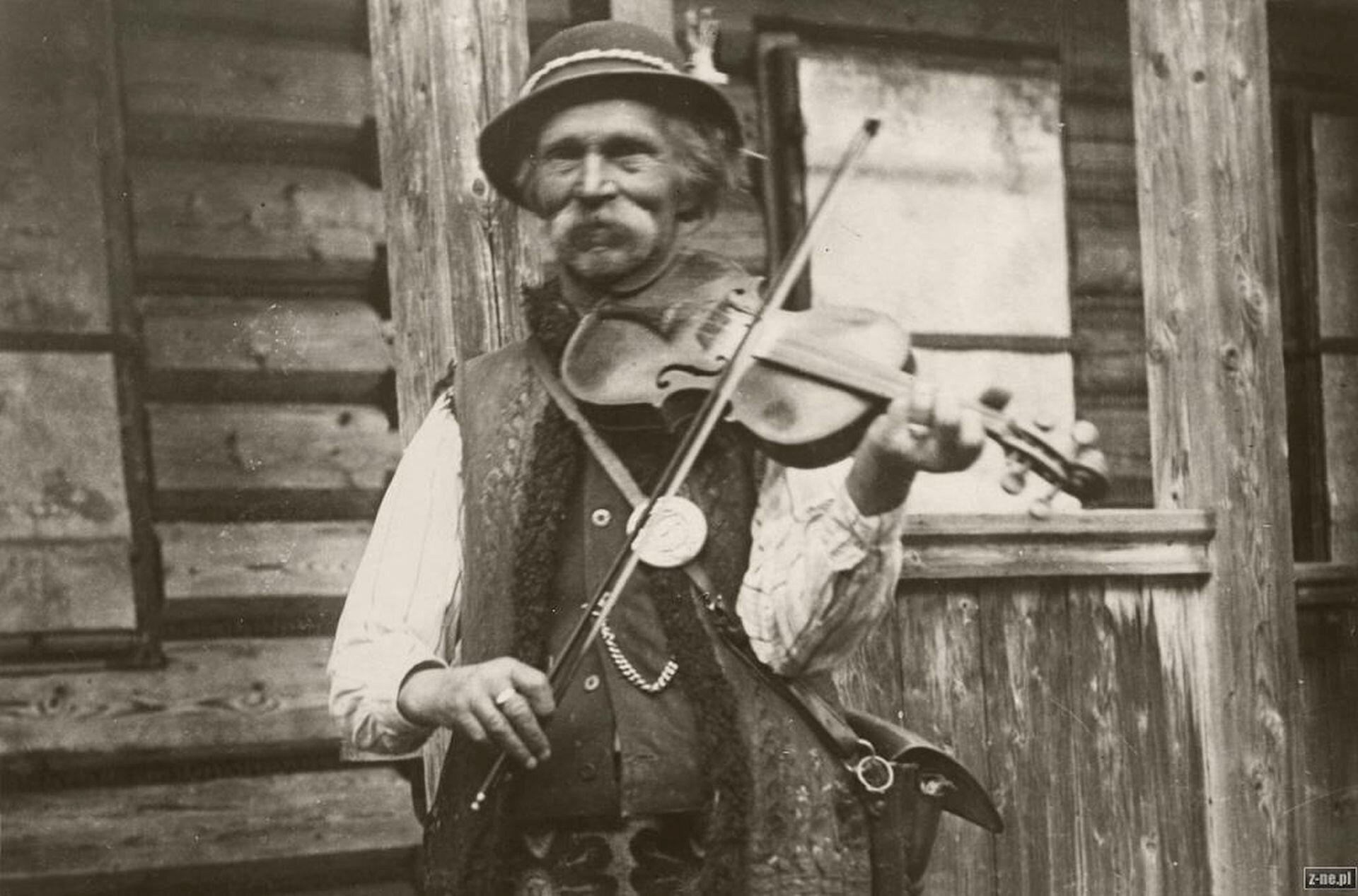 Ilustracja przedstawia Bartka Obrochte ubranego wstrój góralski, grającego na skrzypcach. Mężczyzna ma długie, siwe wąsy.