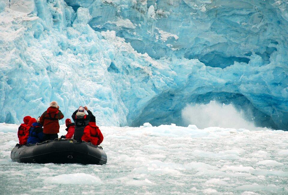 Na zdjęciu lodowiec schodzący bezpośrednio do wód morskich. Widać kawałku lodu wruchu. Spiętrzona woda pokryta krą, ludzie wpontonie fotografują czoło lodowca.