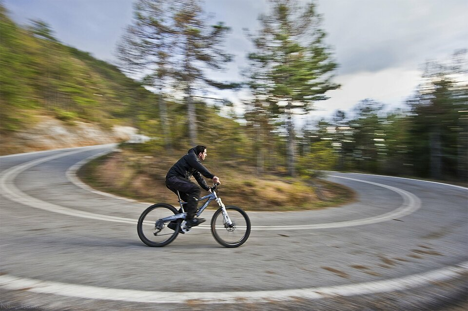 Zdjęcie przedstawia oglądanego zboku rowerzystę wykonującego ciasny skręt wlewo na górskiej drodze. Zakręt jest ostry, wkadrze znajdują się obydwa jego końce. Rozmyte iporuszone wszystkie elementy zdjęcia poza rowerzystą podkreślają wrażenie pędu.