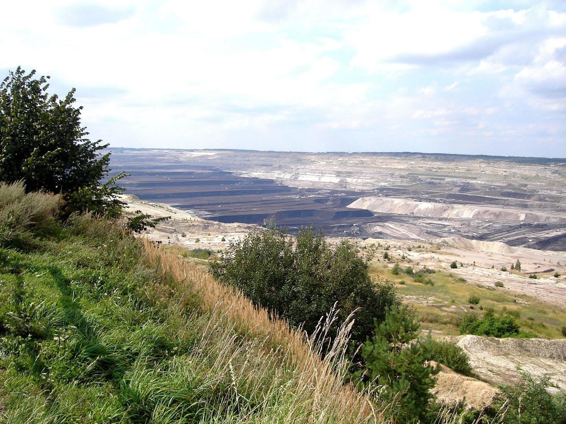Na zdjęciu rozległe wykopy, ziemia odsłonięta warstwami, na dole odkrywki urządzenia ipojazdy.