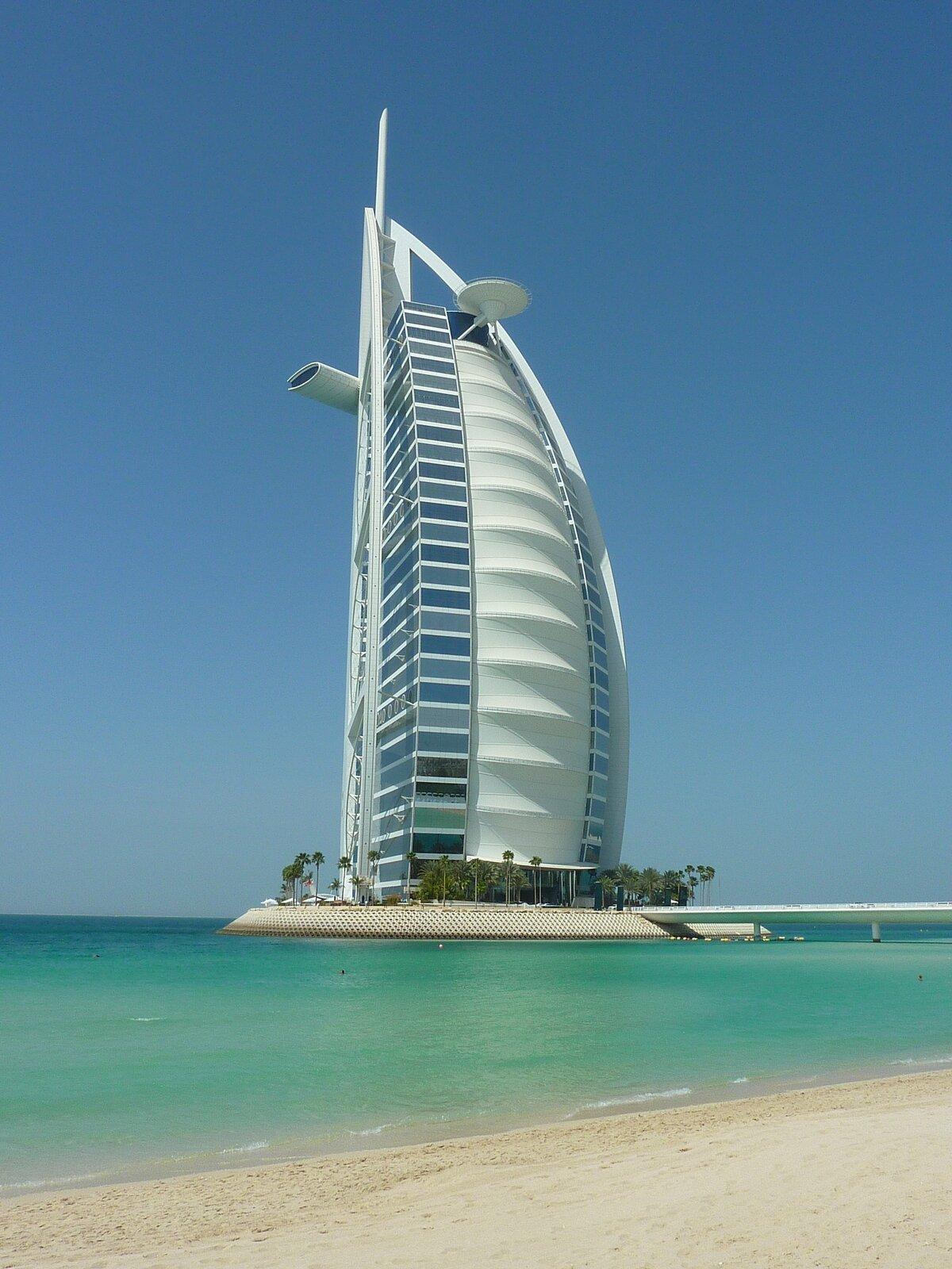 Zdjęcie przedstawia Burdż al-Arab, superluksusowy hotel wDubaju owysokości 321 metrów, przypominający kształtem wielki żagiel. Budynek jest biały, za wyjątkiem wpełni oszklonych narożników istoi na sztucznej wyspie połączonej ze stałym lądem mostem, obecnym na zdjęciu po prawej stronie.