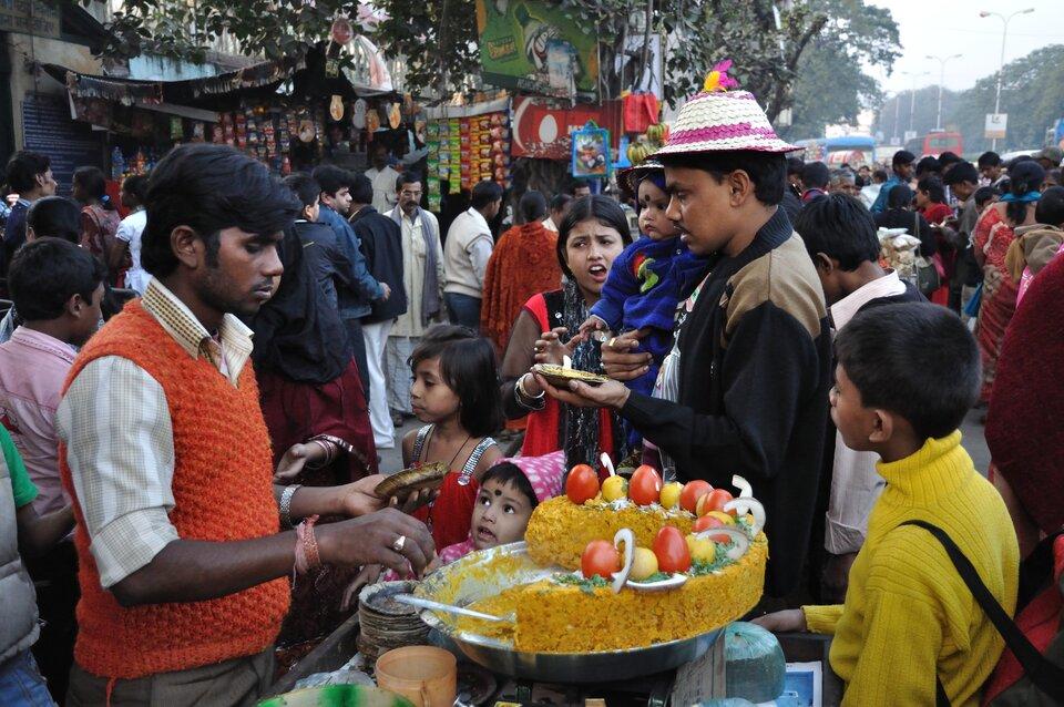 Na zdjęciu zatłoczona ulica Kalkuty. Praktycznie sami ludzie, Hindusi. Na pierwszym planie uliczny sprzedawca jedzenia. Wtle uliczne stragany.