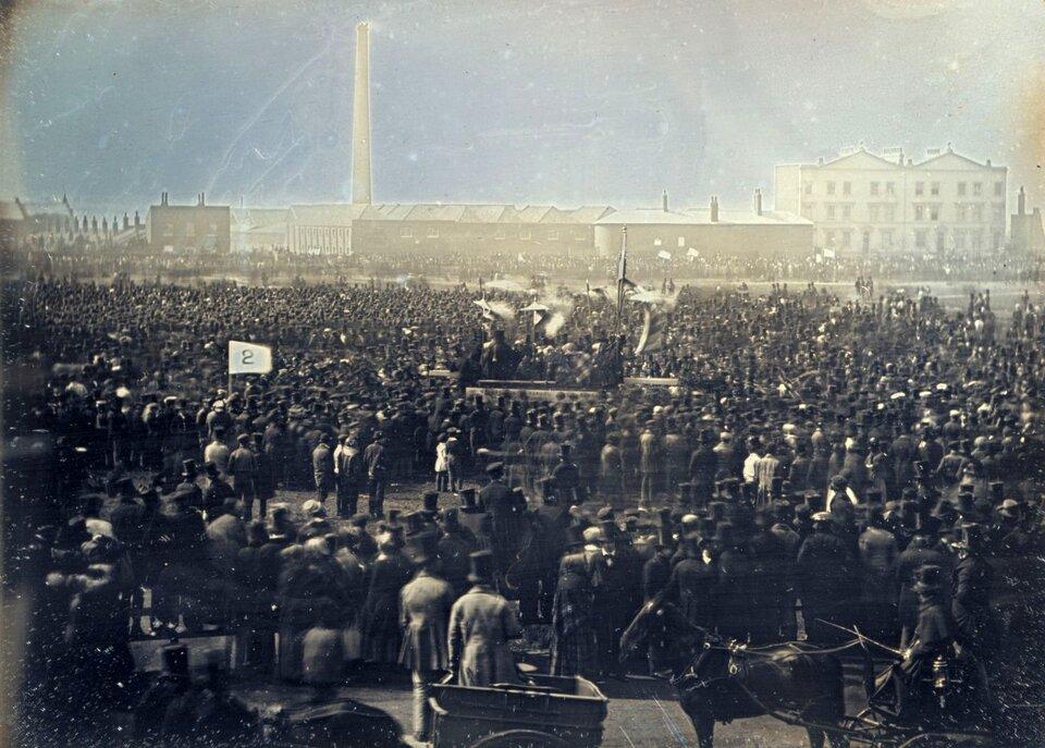 na obrazie, na pierwszym przedstawiono zgromadzenie dużej grupy ludzi, wtle widać zabudowania fabryczne.