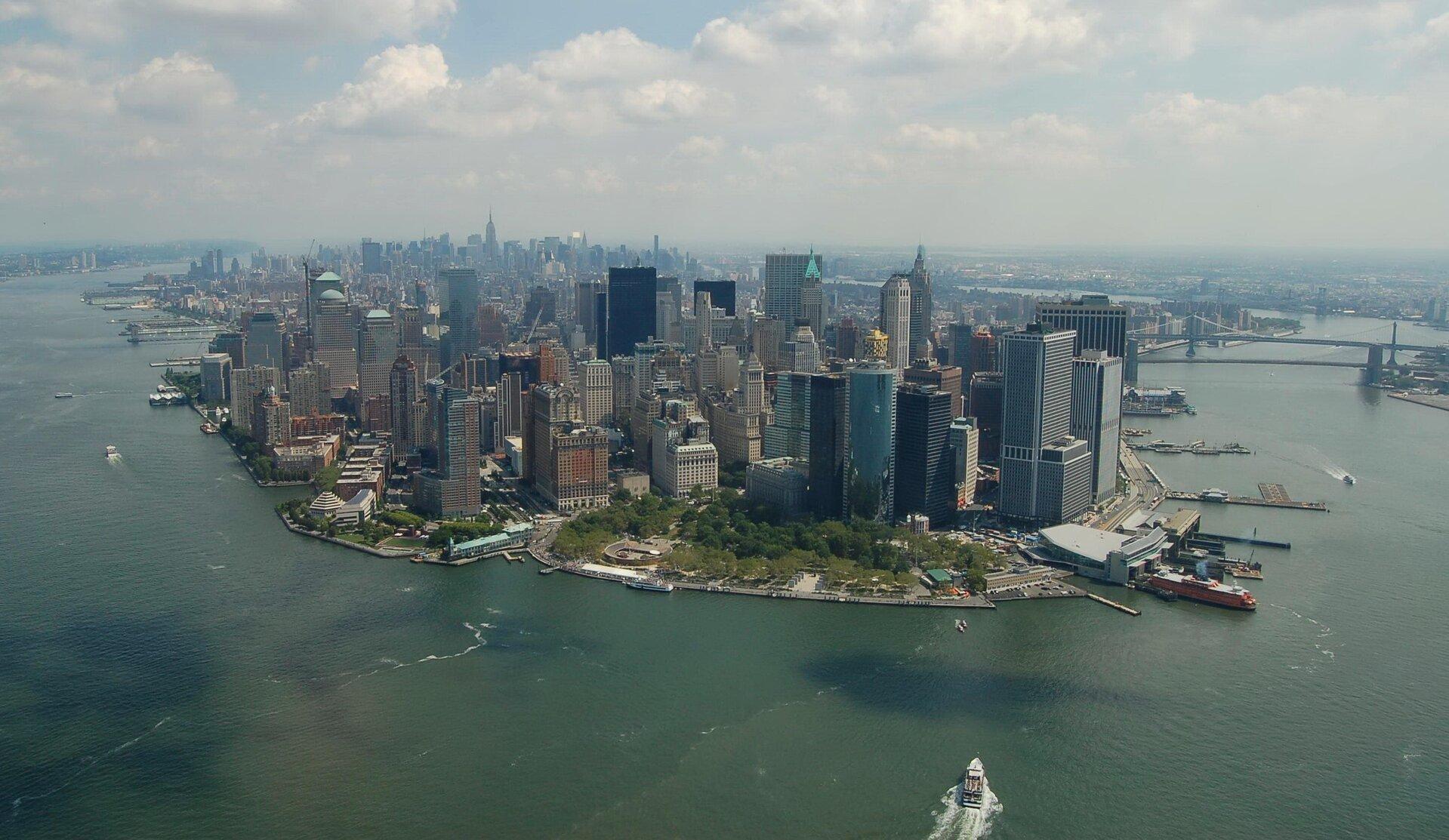 Na zdjęciu lotniczym bardzo gęsta, wysoka, nowoczesna zabudowa miejska usytuowana na końcu cypla otoczonego rzeką. Wtle most na rzece, statki.