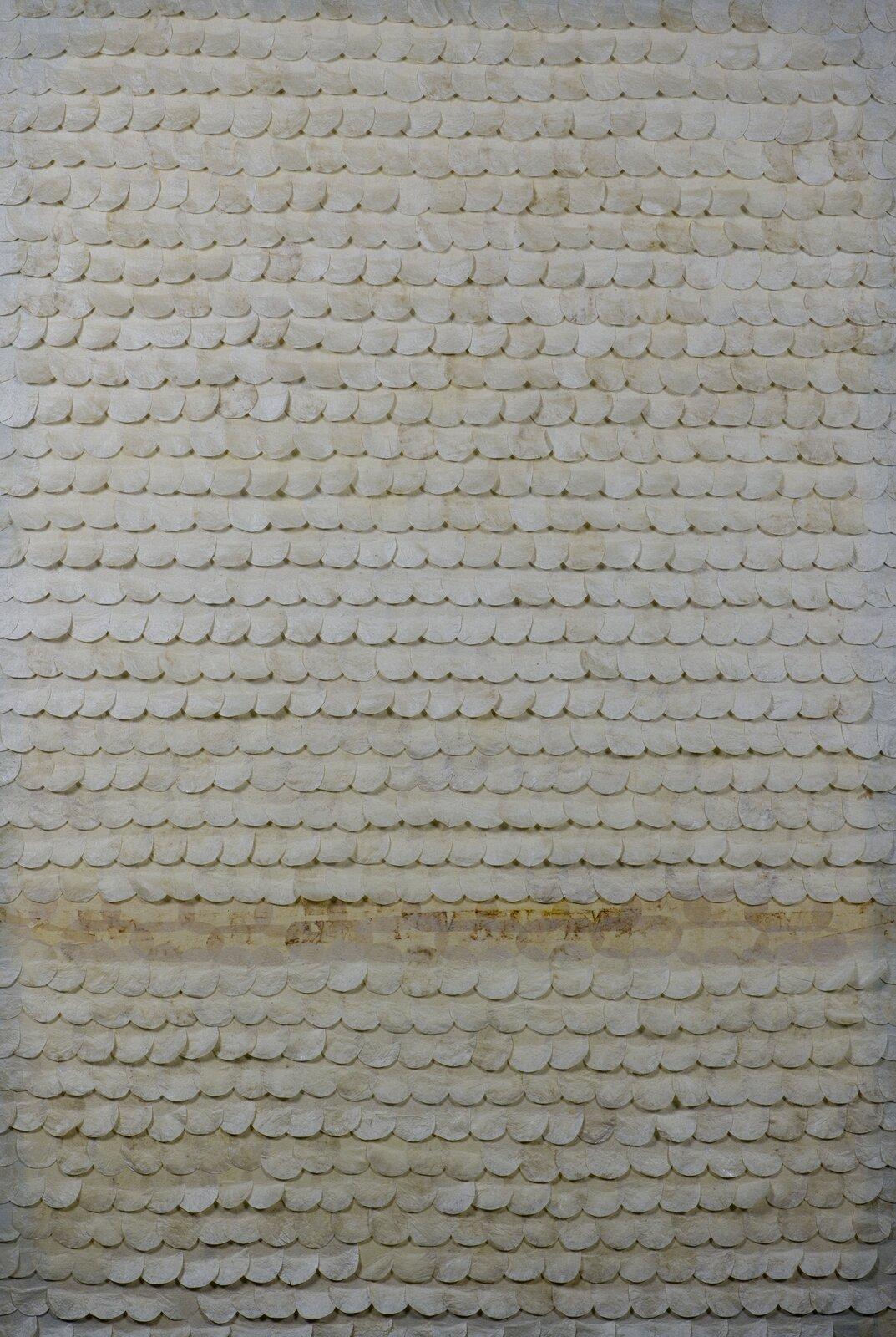 """Ilustracja przedstawia obraz """"Kwitnące I"""" autorstwa Joanny Chołaścińskiej. Na jasno-beżowym tle poprzyklejane zostały rzędy półokrągłych karteczek wkształcie łusek oniejednolitej, biało-beżowej powierzchni. Wdolnej partii obrazu, między rzędami znajduje się przerwa znieczytelnym, poprzecieranym, brązowym napisem. Monochromatyczna, statyczna kompozycja utrzymana jest wbeżowej tonacji barw."""