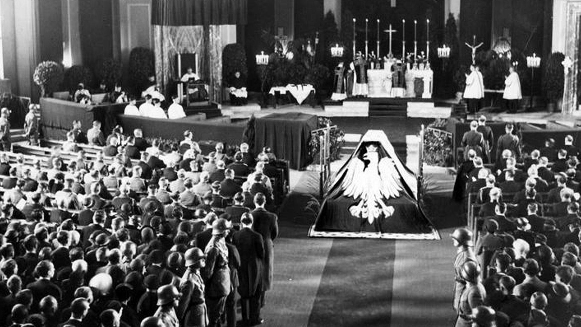 """Czarno-biała fotografia przedstawia wnętrze wypełnionego ludźmi kościoła. Zdjęcie zrobione zostało od strony wejścia do świątyni. Wcentrum znajduje się ołtarz ikapłani odprawiający mszę. Na podłodze wkierunku ołtarza, przez środek kościoła leży dywan. Na dywanie przed ołtarzem na katafalku umieszczona jest trumna przykryta materiałem. Na katafalku umieszczono pośrodku dużą figurę białego orła wkoronie zgodła Polski. Po obu stronach dywanu stoi szpaler umundurowanych żołnierzy wstalowych hełmach charakterystycznych dla armii niemieckiej zlat 30-tych. Ławki po prawej ilewej stronie wypełnione są uczestnikami uroczystości. Pod zdjęciem umieszczono informację dotyczącą przedstawionego wydarzenia: """"Msza żałobna za duszę zmarłego Józefa Piłsudskiego wkatedrze św. Jadwigi wBerlinie, 18 maja 1935 r. Wpierwszym rzędzie po lewej (obok symbolicznej trumny) kanclerz Rzeszy Adolf Hitler.""""."""