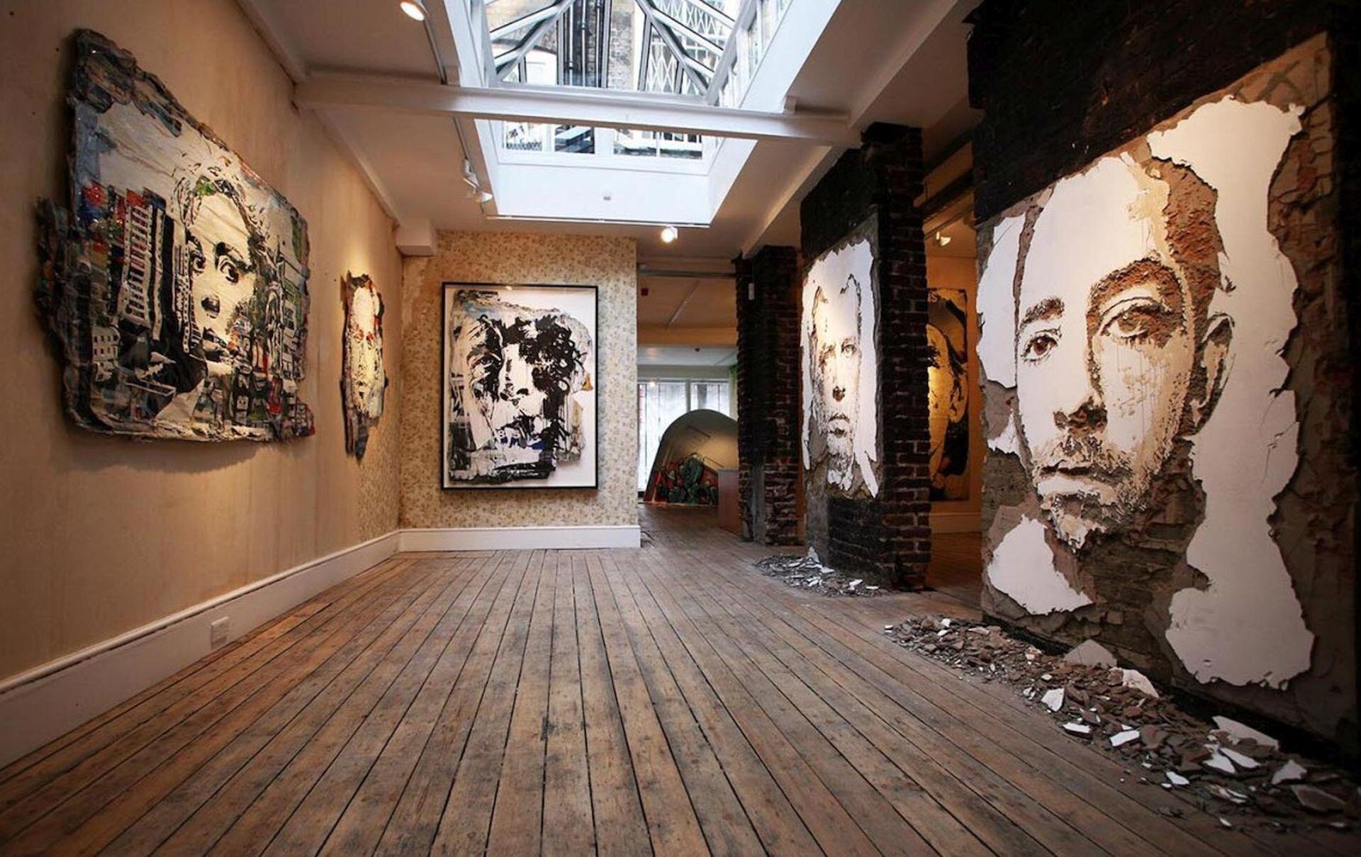 Zdjęcie przedstawia wnętrze galerii. Na ścianach ukazane są graffiti przedstawiające twarze.