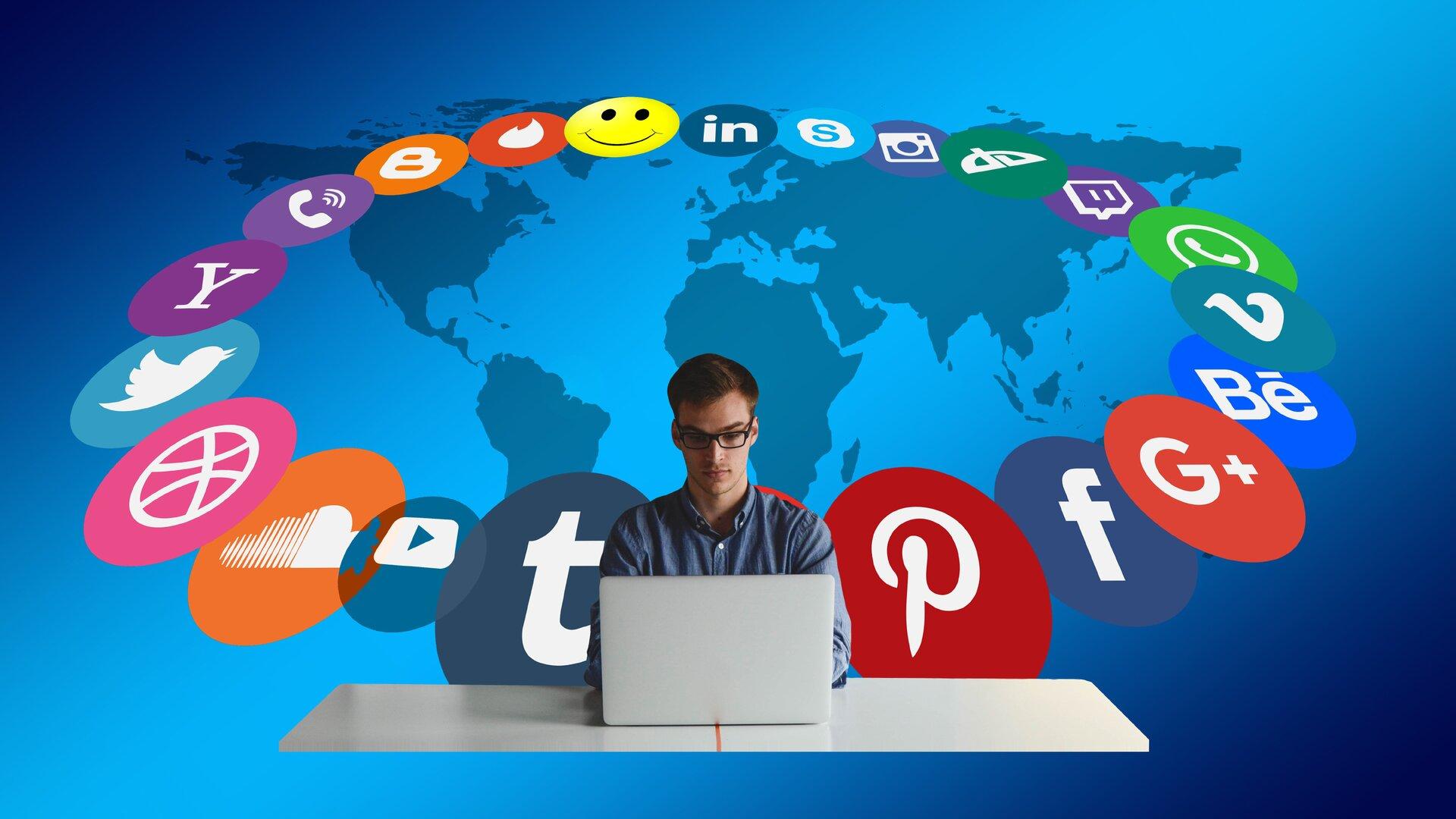 Ilustracja przedstawia młodego mężczyznę siedzącego przy biurku przed otwartym laptopem. Mężczyzna ma ciemne krótkie włosy, okulary wciemnych oprawkach oraz niebieską koszulę. Laptop ma obudowę wkolorze białym iwidać wyłącznie jego tylną część. Biurko jest puste iwidać wyłącznie jego biały blat. Za mężczyzną znajduje się niebieskie tło, na którym został przedstawiony zarys mapy świata. Mapę świata otacza krąg złożony zlogotypów znanych aplikacji istron internetowych, na przykład logotypu portalu Facebook, Pinterest, Twitter.