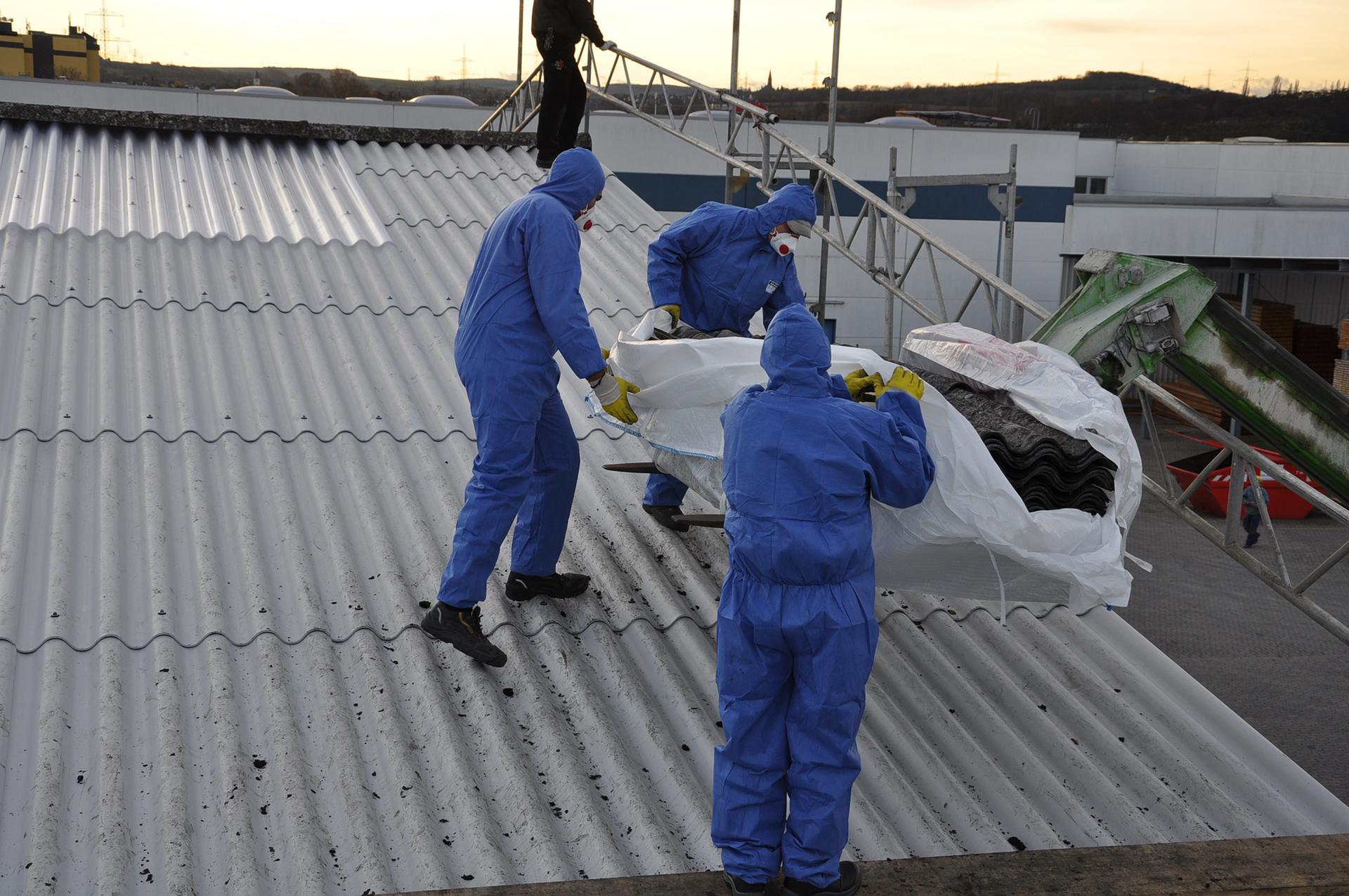 Azbest jest włóknem mineralnym, które zuwagi na jego bardzo szkodliwe działanie (pylica azbestowa, nowotwory) zostało wycofane zużytku (w Polsce w1997 r.). Prowadzone są na szeroką skalę działania, mające na celu wyeliminowanie azbestu iwyrobów zawierających azbest znaszego otoczenia. Fotografia przedstawia wymianę dachu pokrytego bardzo popularnym kiedyś eternitem azbestowo-cementowym – materiałem budowlanym wykorzystywanym dawniej wbudownictwie wpostaci płyt pokryciowych