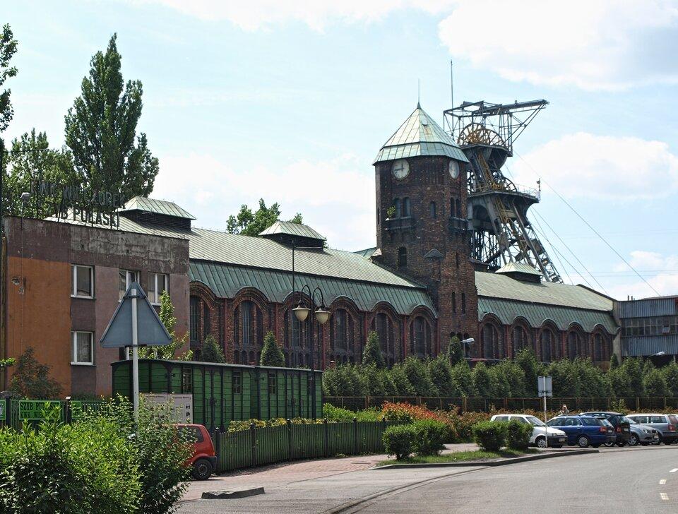 Na zdjęciu ceglany budynek zwieżą. Wtle wieża szybowa – wysoka konstrukcja stalowa zkołami. Przed budynkiem zaparkowane samochody.