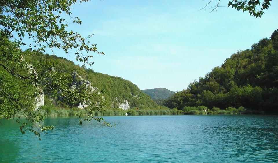 Na zdjęciu zbiornik wodny, na brzegu lasy liściaste.