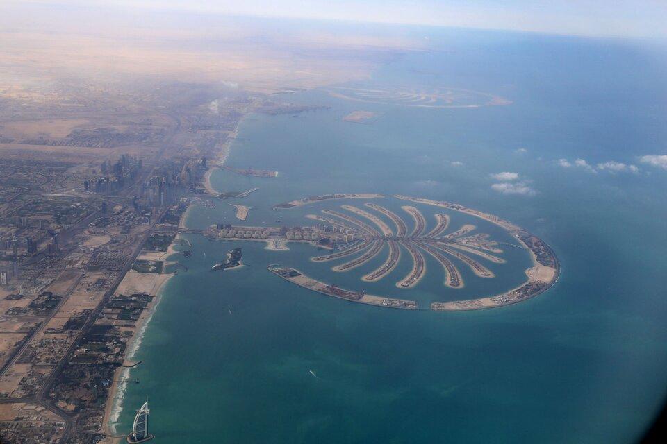 Na zdjęciu lotniczym brzeg morski, zlewej strony stały ląd, zabudowania. Zprawej strony wmorzu wyspa wkształcie palmy, poszczególne liście łączą się na środku iprzechodzą wpień palmy, który łączy się ze stałym lądem.