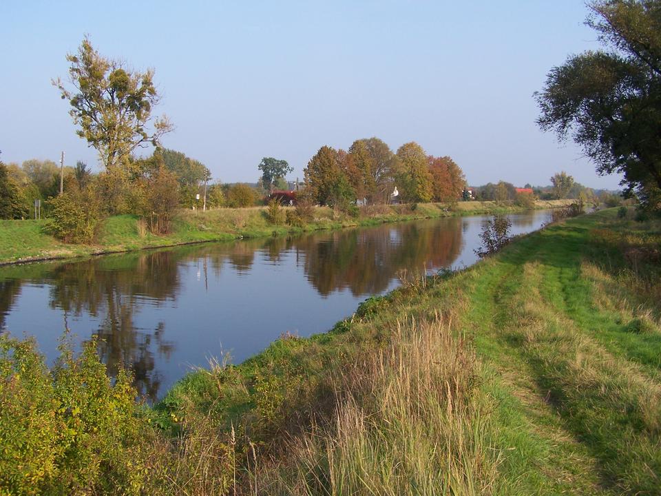 Fotografia prezentuje Kanał Gliwicki. Widać, prosty bieg kanału wypełnionego wodą. Nad kanałem rosną drzewa ikrzewy.