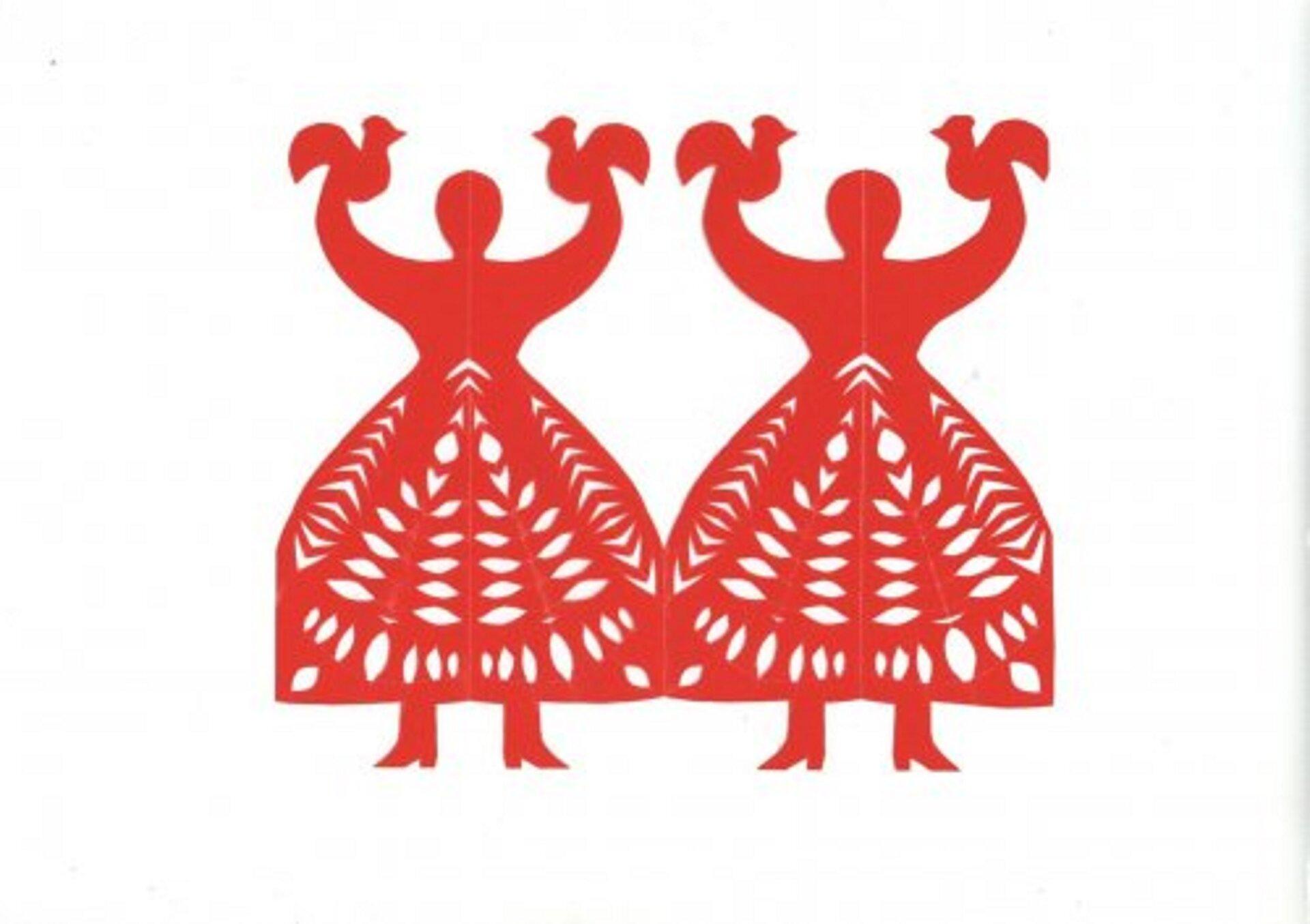 Ilustracja przedstawia wycinankę kołbielską kobiety zkokoszkami. Wycinanka to dwie kobiety stojące istykające się dołem rozkloszowanymi sukniami. Trzymają ręce wgórze, na których widać koguciki. Wycinanka ma kolor czerwony.