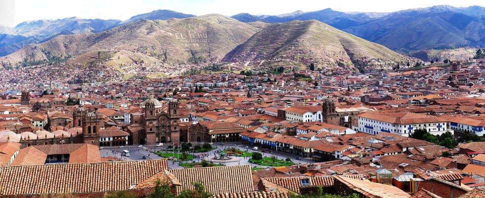 Na zdjęciu miasto ustóp gór, bardzo gęsta niska zabudowa, czerwone dachy, kwadratowy plac zwysokim budynkiem zwieżami.