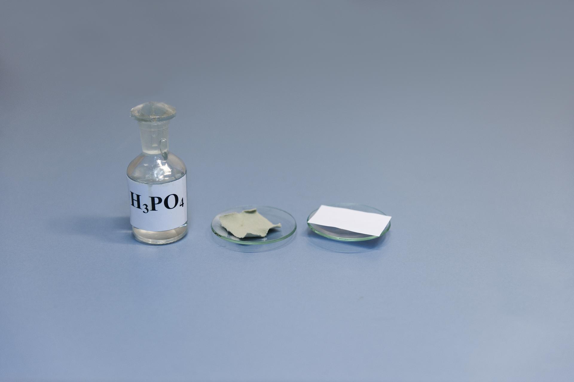 Pierwsze zdjęcie wgalerii. Na ilustracji prezentowana jest szklana butelka zetykietką inapisem H3PO4 stojąca na niebieskim podłożu. Po jej prawej stronie na blacie laboratoryjnym stoją wszeregu dwa szkiełka zegarkowe zawierające kolejno: kawałek tkaniny iskrawek papieru.