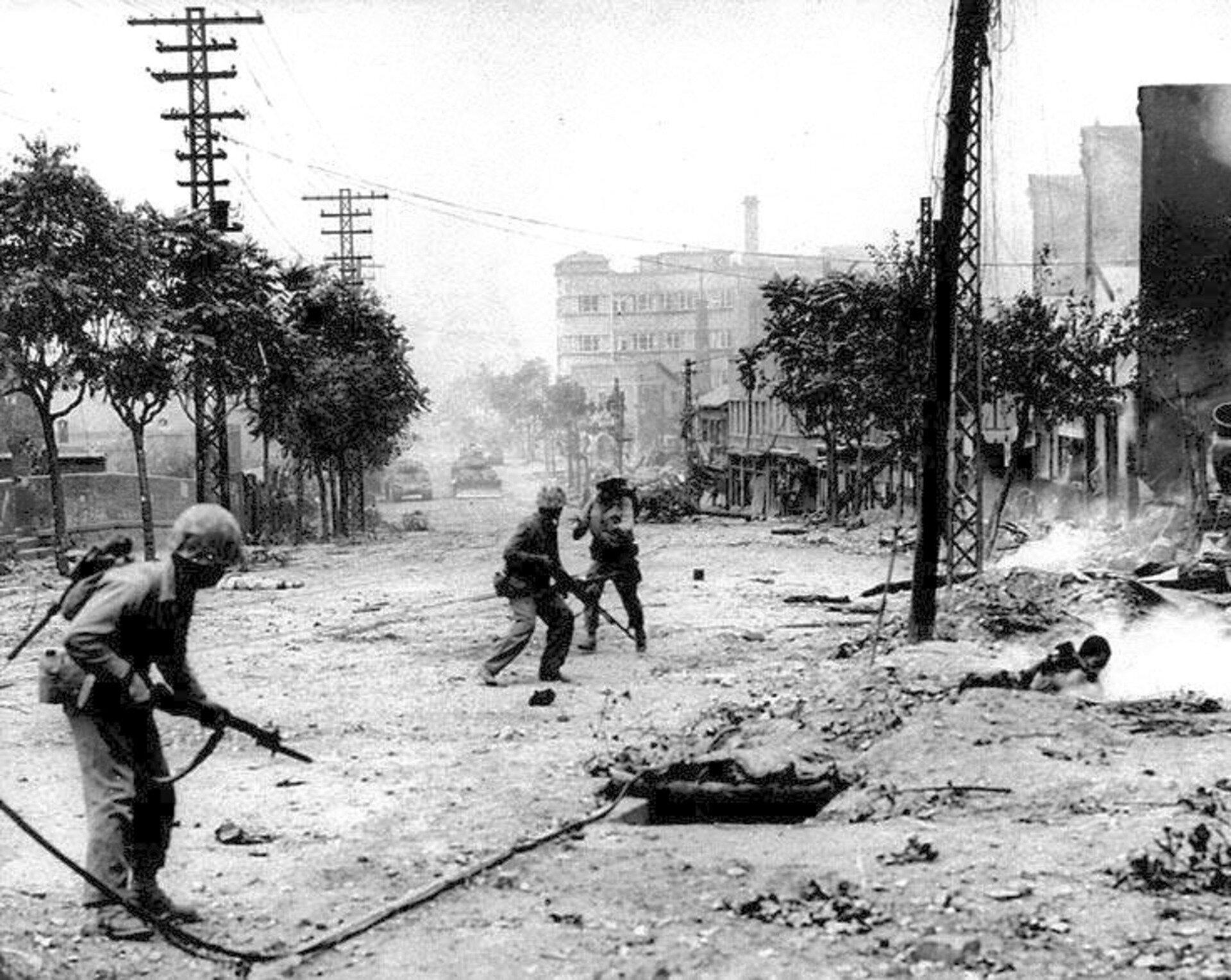 Fotografia czarno-biała przedstawiająca fragment ataku na zniszczone miasto. Na pierwszym planie widać kilku żołnierzy szturmujących miasto. Na głowach mają hełmy wrękach karabiny. Celują nimi wotwór studzienki kanalizacyjnej wdrodze jakby miałby wniej być wróg. Ulice są zniszczone, zbombardowane, widać kłęby brudu, kurzu igruzu.