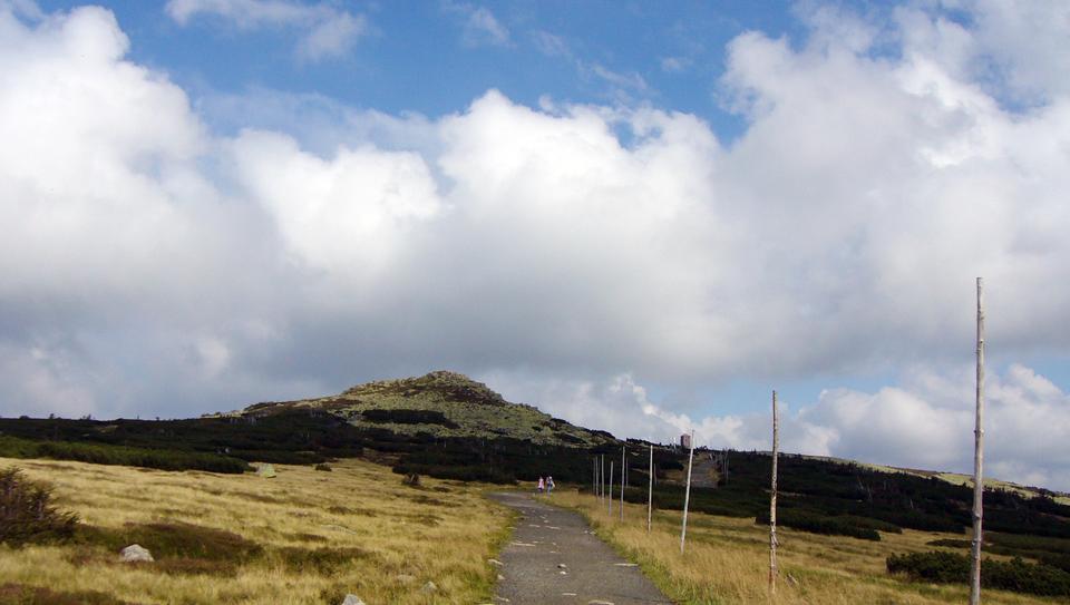Fotografia prezentuje szlak górski wzdłuż, którego po prawej stronie stoją wysokie tyczki. Po obu stronach szlaku teren porośnięty trawą oraz niskimi krzewami. Woddali widoczna góry ołagodnym szczycie.