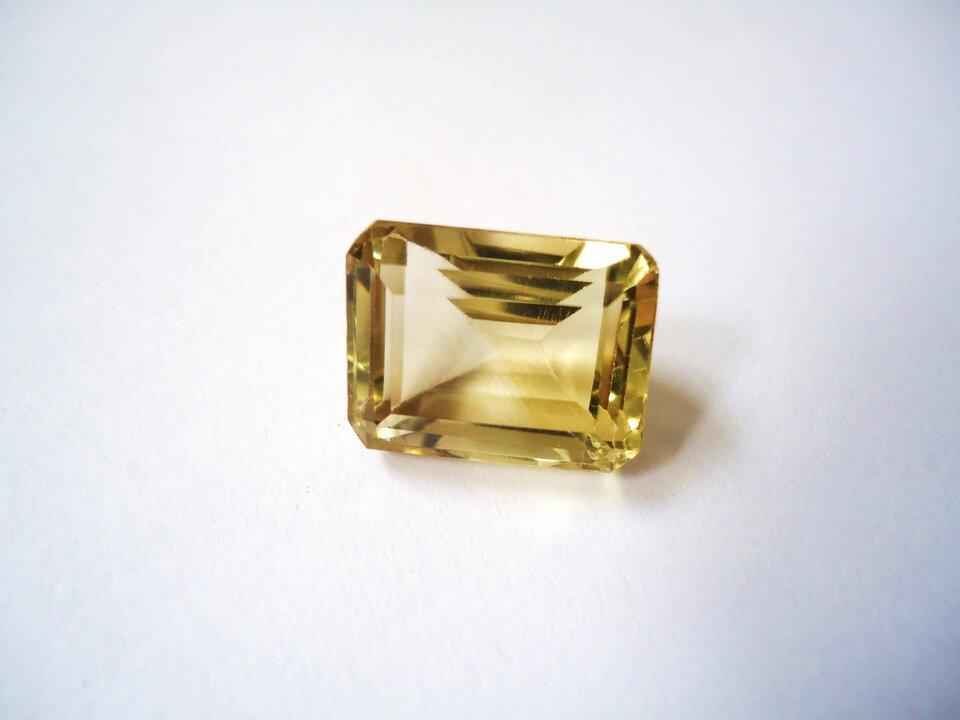 Zdjęcie przedstawia oszlifowany cytryn wformie szlifu szmaragdowego, czyli prostokątnego. Kamień jest jasnożółty ilekko przejrzysty, leży na białym tle.