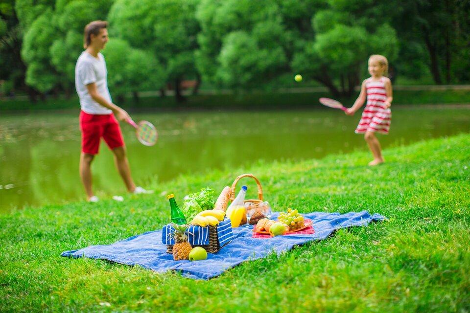 Fotografia przedstawia dziewczynkę zbratem lub tatą podczas aktywnego wypoczynku na łonie natury, połączonego zpiknikiem. Na pierwszym tle koc zkoszami piknikowymi wypełnionymi pożywieniem. Na drugim tle - toczy się gra, polegająca na odbijaniu piłki za pomocą paletek.
