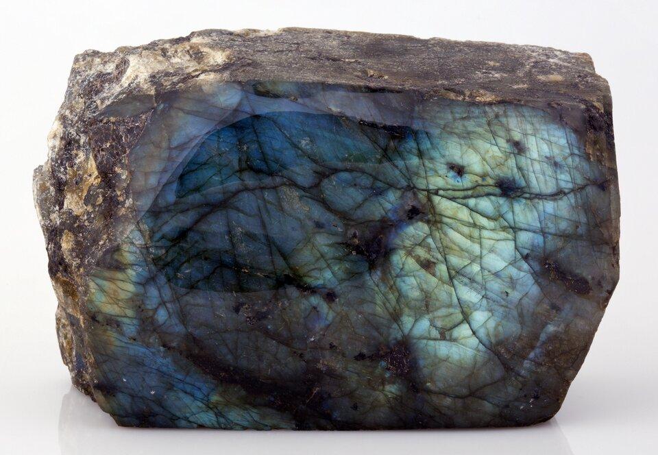 Na zdjęciu minerał. Jest to labradoryt. Ma kształt równego prostokątnego kamienia. Jest przekrojony, widać wnętrze. Na zewnątrz brązowy, matowy, szorstki. Wewnątrz szklisty. Zlewej strony ciemnoniebieski, zprawej strony jaśniejszy. Widać spękania, czarne kreski.
