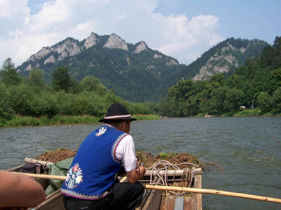 Na zdjęciu flisak wstroju ludowym na barce płynącej po rzece. Wtle góry oskalistych szczytach.
