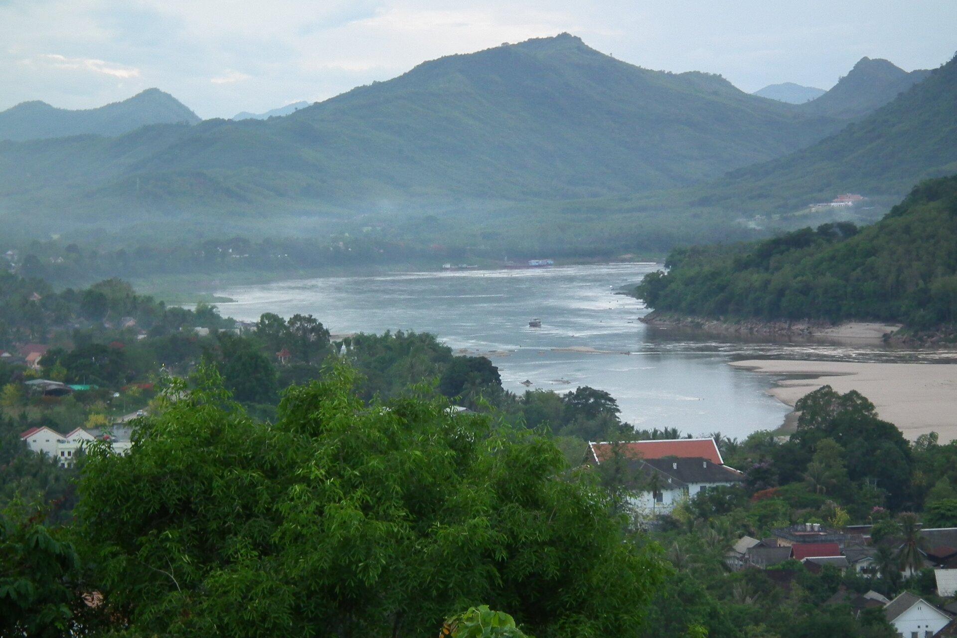 Na zdjęciu szeroka rzeka wrozległej dolinie. Wtle góry. Na pierwszym planie zabudowania mieszkalne.