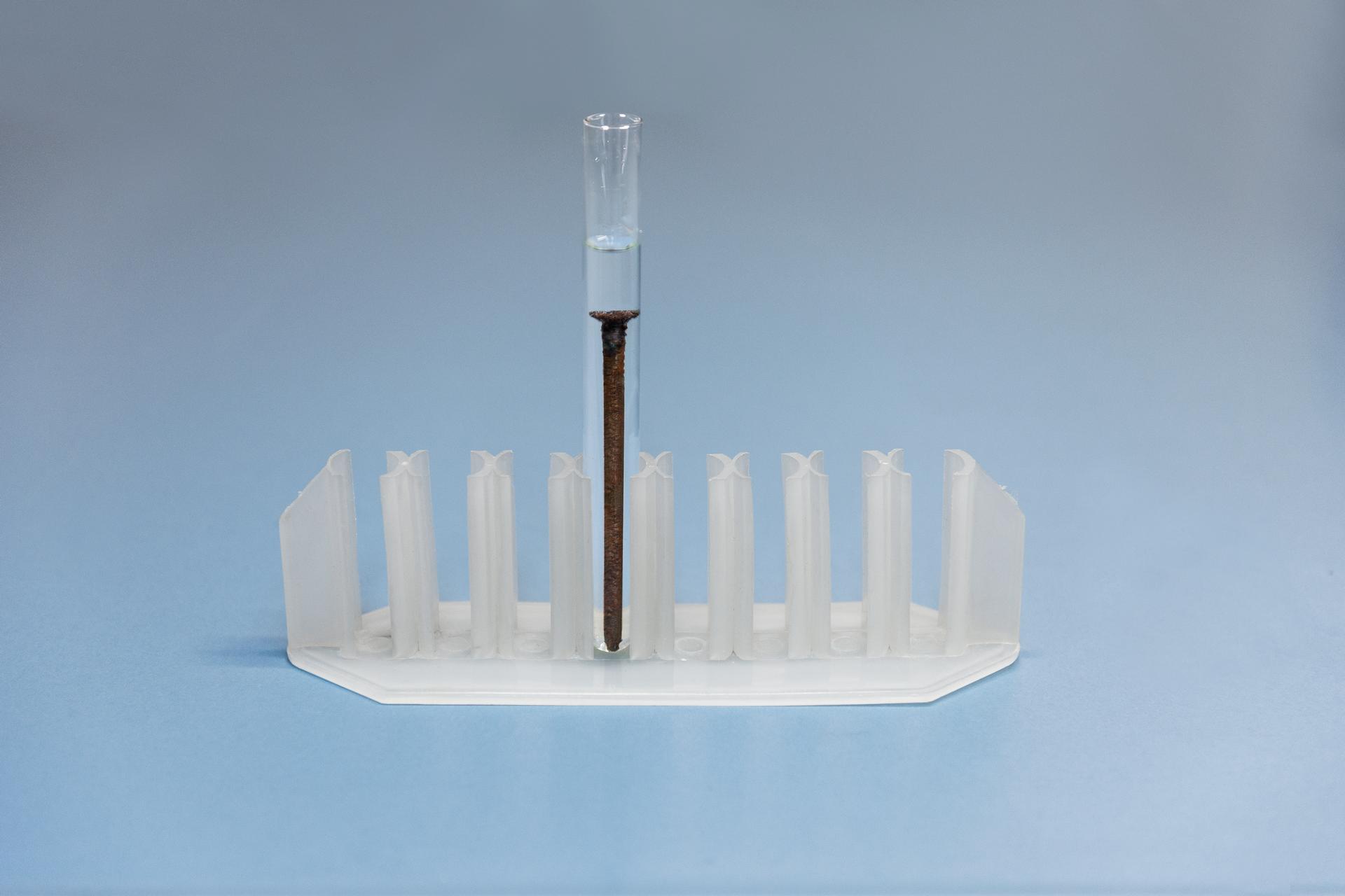 Trzecie zdjęcie wgalerii przedstawia plastikowy stojak na probówki zjedną małą probówką. Probówka napełniona jest kwasem fosforowym, do którego wrzucono duży, zardzewiały gwóźdź.