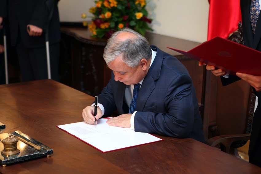 Prezydent Rzeczypospolitej Polskiej Lech Kaczyński podpisuje ustawę zdnia 7 września 2007 r. oKarcie Polaka podczas III Zjazdu Polonii iPolaków zZagranicy.