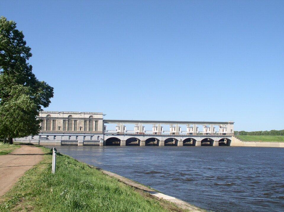 Na zdjęciu zapora na rzece. Duży budynek na brzegu rzeki, dalej betonowa budowla hydrotechniczna, przegradzająca dolinę rzeki wcelu spiętrzenia wody.
