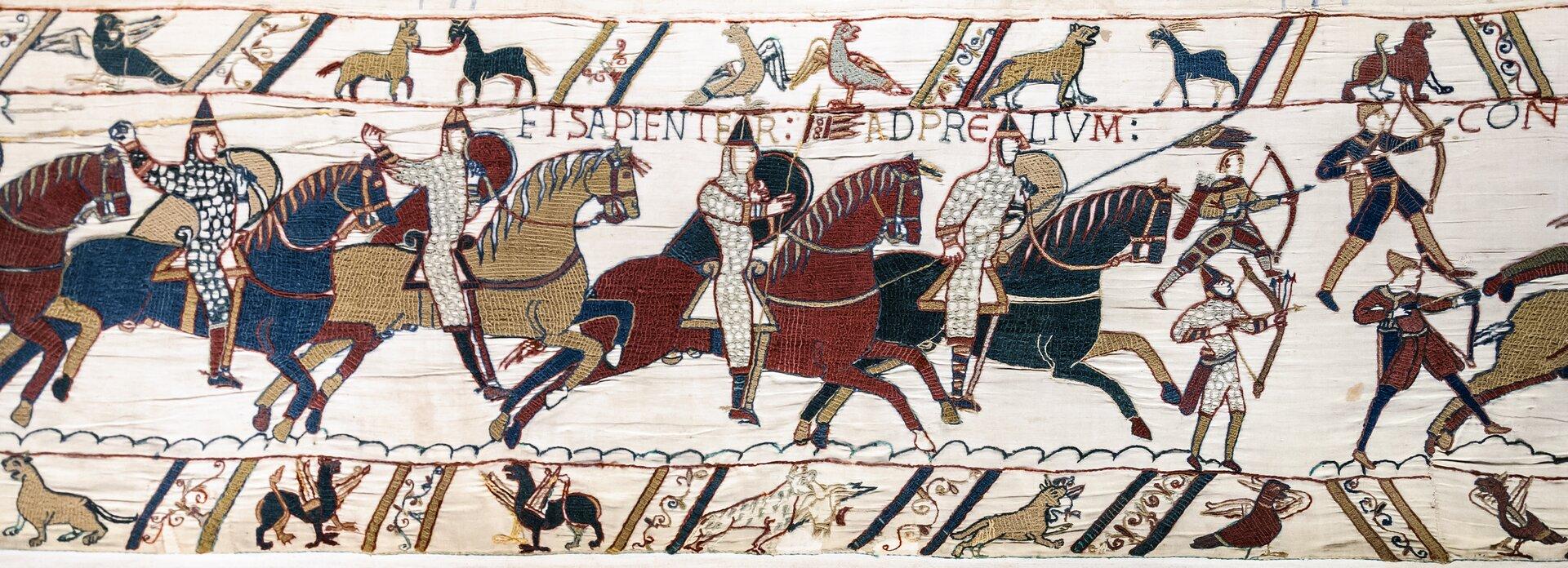 Ilustracja przedstawia fragment tkaniny zBayeux. Ukazuje podbój Anglii przez Wilhelma Pierwszego Zdobywcę. Na ilustracji przedstawieni są rycerze na koniach. Po prawej stronie stoi czterech łuczników. Po lewej stronie konno jadą rycerze zpodniesionymi rękoma. Nad nimi zamieszczony jest pas zsymbolami zwierzęcymi oraz napis wjęzyku łacińskim. Na dole ukazane są miniatury ze sceny walki.