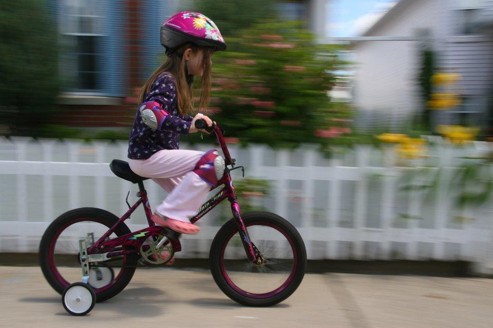 Fotografia przedstawia dziewczynkę jadącą rowerem. Dziewczynka jest wyposażona wkask ochronny, nakolanniki oraz nałokietniki.