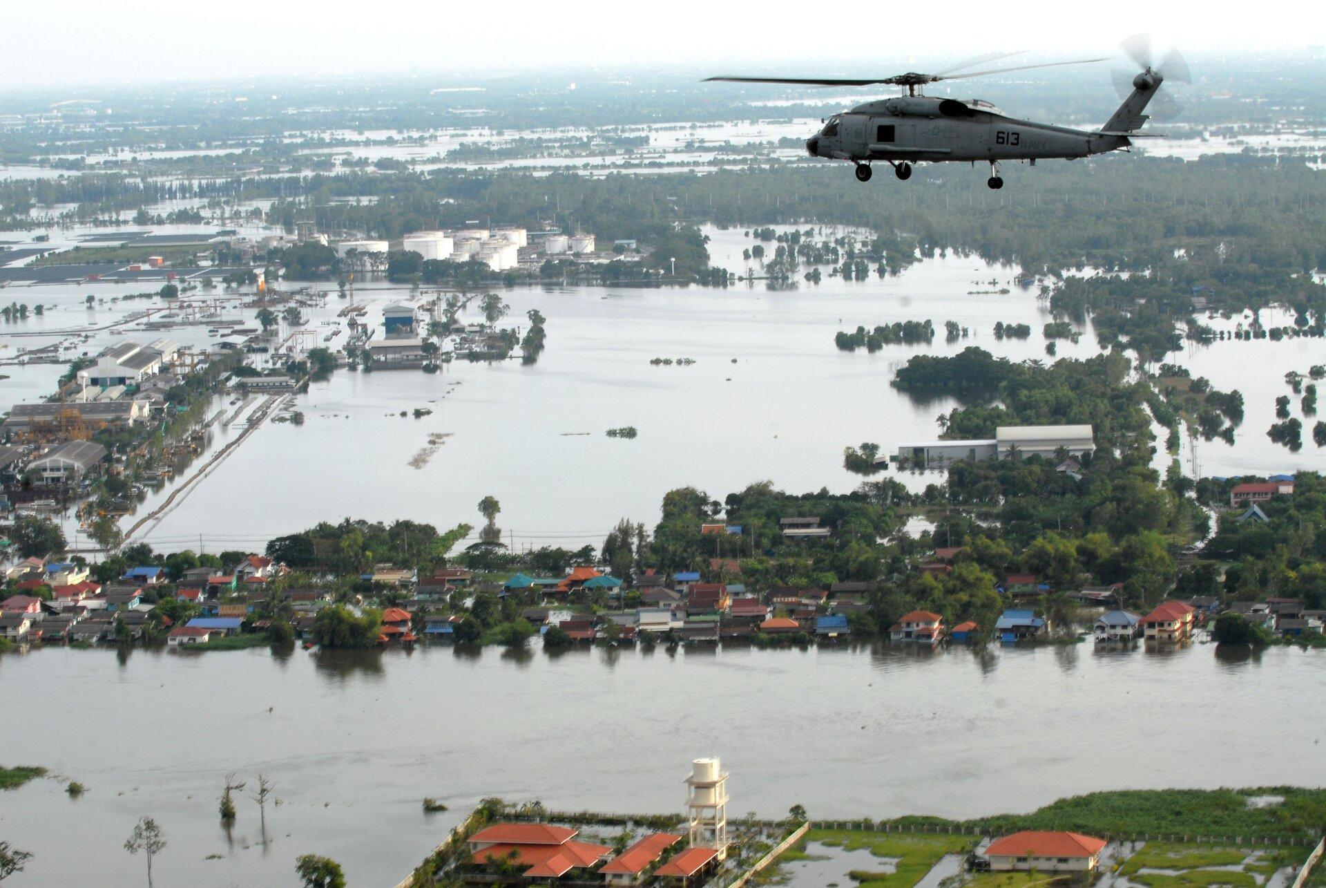 Na zdjęciu równiny teren zalany przez powódź. Zabudowania wwodzie. Wpowietrzu śmigłowiec.