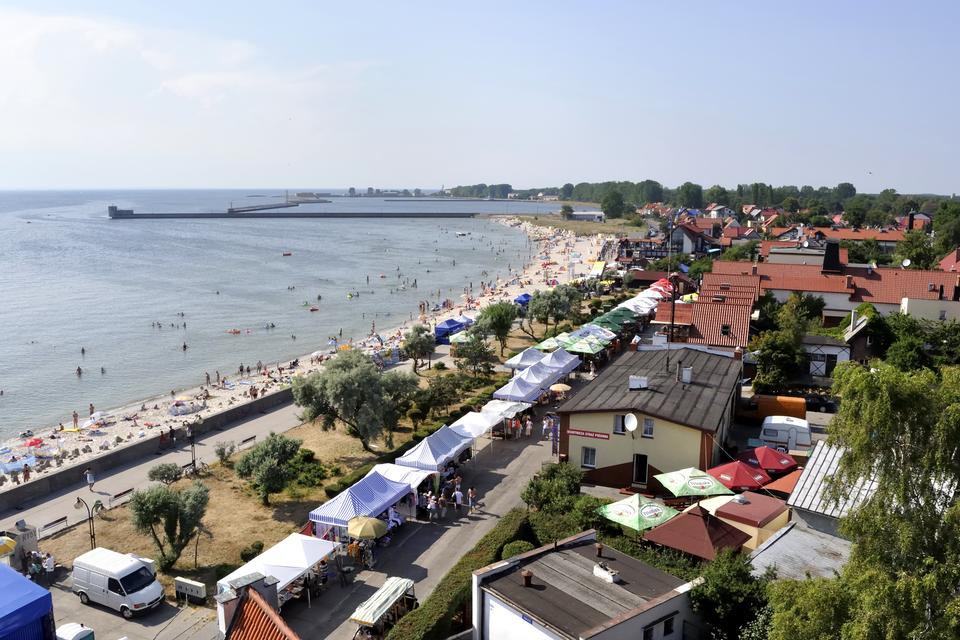 Fotografia zHelu, widoczne wybrzeże morza zplażą oraz licznymi budynkami wzdłuż drogi.