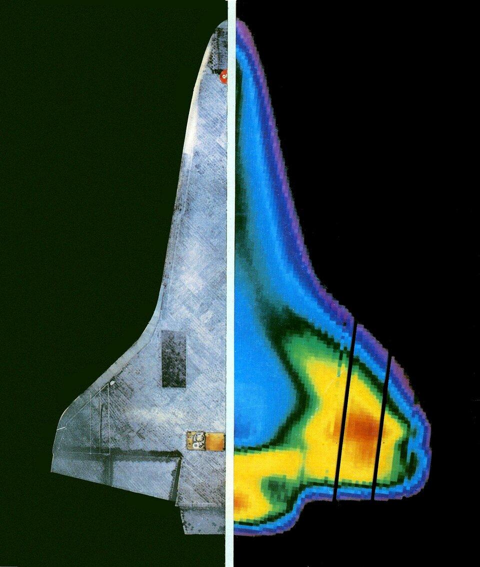 Ilustracja przedstawia prom kosmiczny ustawiony pionowo. Kokpit pilota znajduje się na górze ilustracji. Koniec samolotu na dole. Samolot kosmiczny ma kształt trójkąta ozaokrąglonych wierzchołkach. Samolot podzielony wpionie białą linią na dwie równe części. Lewa część samolotu ma kolor szary. Prawa strona samolotu to obraz uzyskany przez kamerę termowizyjną. Kolory wskazują na wysokość temperatury. Górna część samolotu ikrawędzie mają kolor niebieski. Kolor niebieski to wskaźnik wysokiej temperatury. Dolna połowa samolotu iskrzydło to kolor żółty. Żółty wskazuje na niższą temperaturę. Środkowa część skrzydła ma kolor czerwony. Kolor czerwony oznacza temperaturę wyższą niż temperatura powierzchni promu wkolorze żółtym, niższą jednak od obszaru niebieskiego.